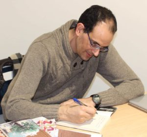 Miguel Ángel Rubio firmando ejemplares de su libro, Geografía de la luz